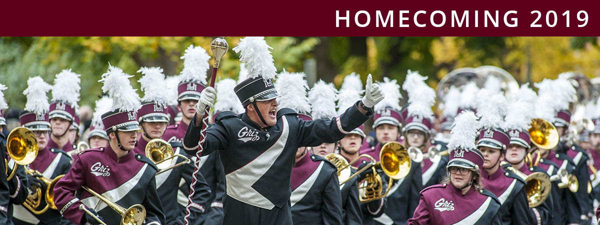 Picture of University band in parade. Text reads: Homecoming 2019