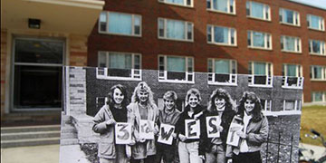Black and white photos of students from the past being held up in front of Craig Hall