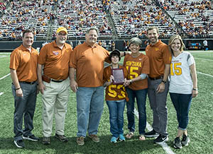 Paolis onfootball field with University dignitaries receiving award