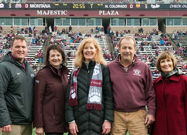 Picture of Julie and Sam Baldridge with campus dignitaries on football field