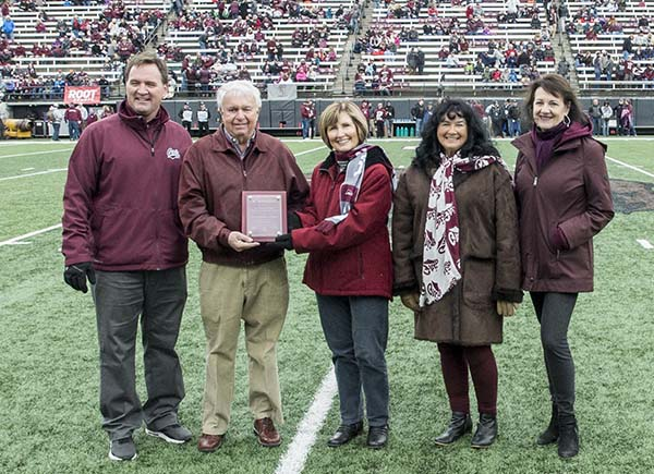Picture of Cal and Marva Christian with campus dignitaries on football field
