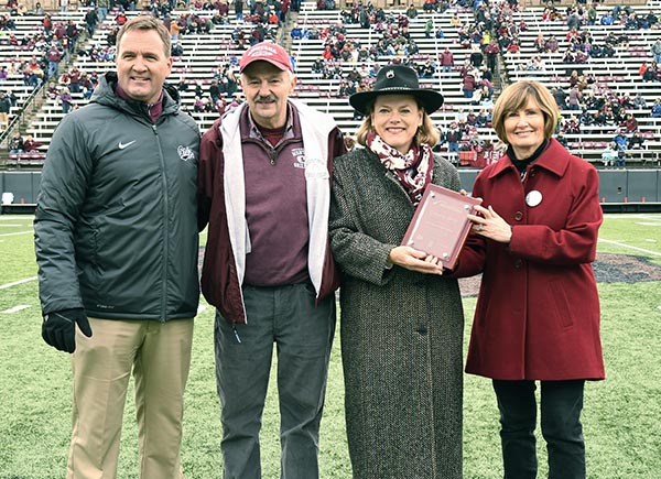 Picture of Don and Patty Cowles with campus dignitaries on football field
