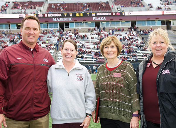 Picture of Janet McDonald with campus dignitaries on football field
