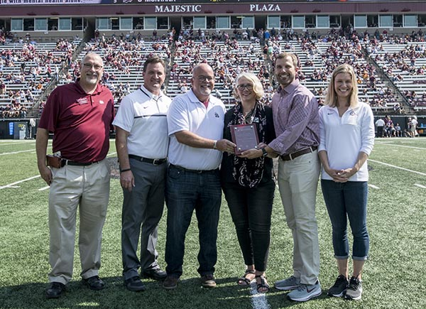 Picture of Bill and Dori Johnston on field with University administrators