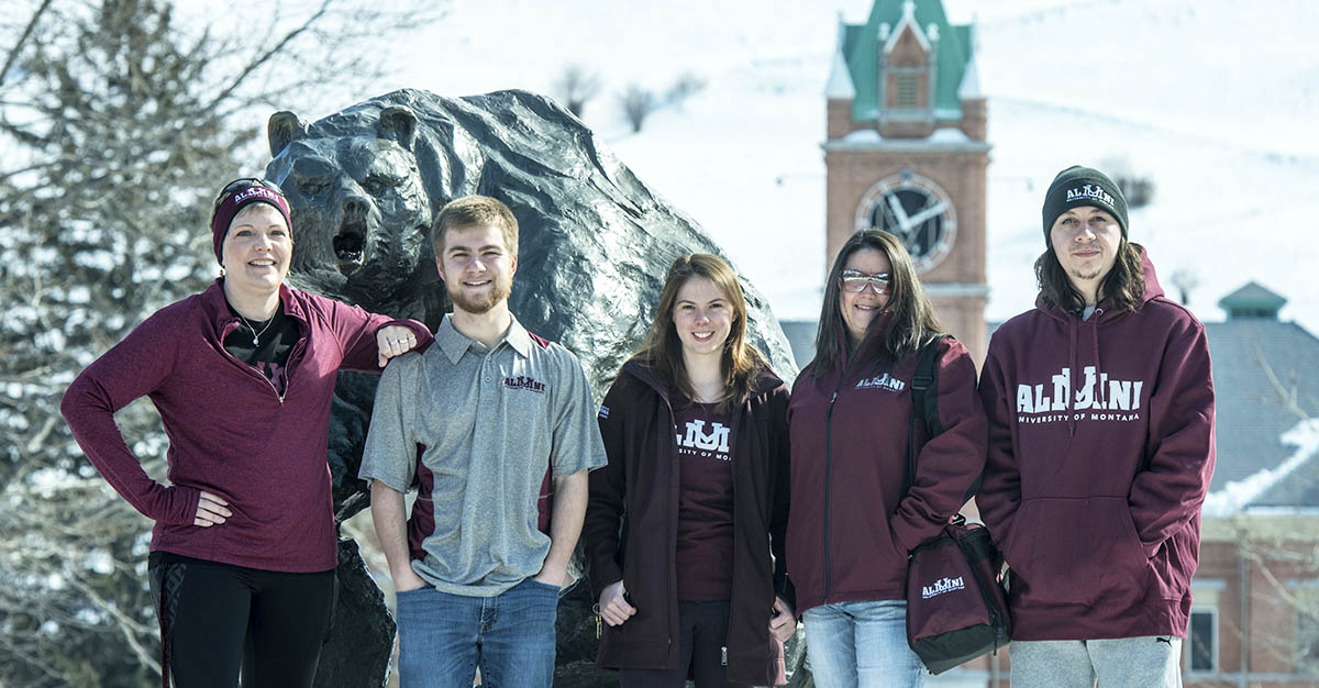 People standing in front of Griz statue wearing UM Alumni clothing