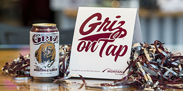 Picture of Griz on Tap table tent with can of Griz Lager and pom pom